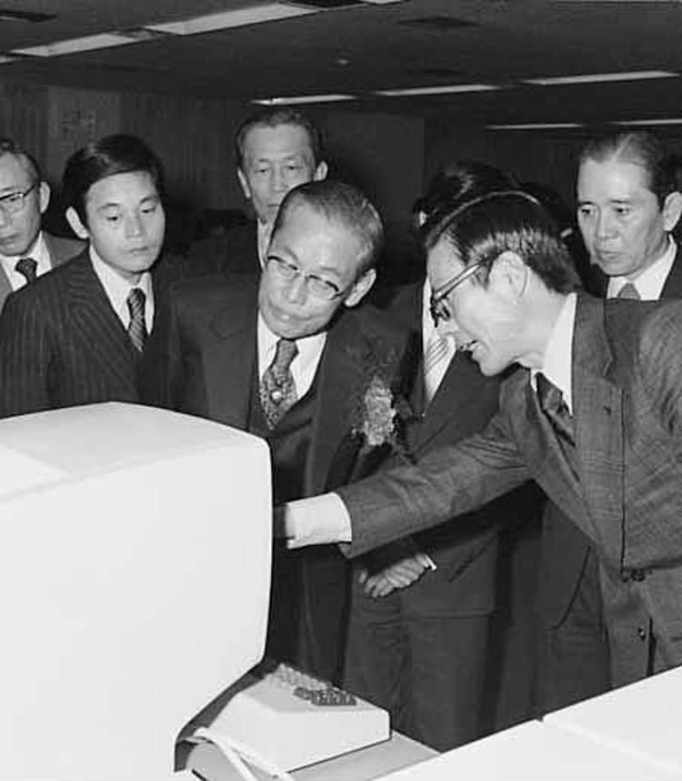 Cap 9: Ông Lee Kun-hee (trái) và cha ông Lee Byung-chull, nghe một kỹ sư Samsung trình bày về hệ thống máy tính năm 1976